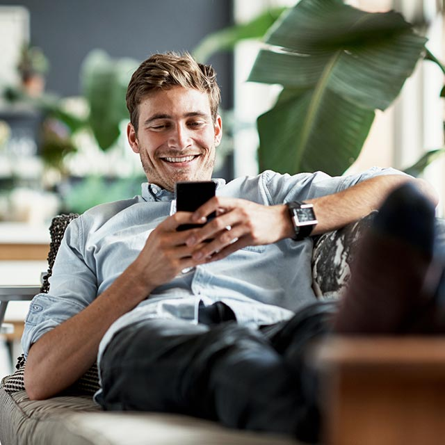 Man on a couch using a mobile phone